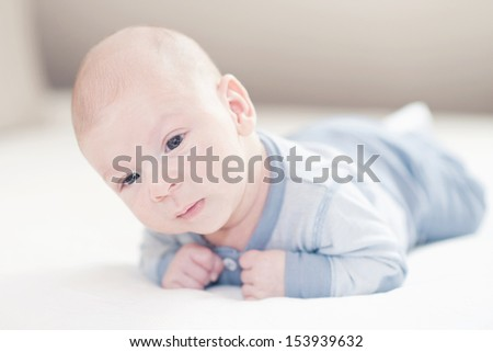 Charming newborn baby boy in blue on a bed