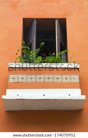 charming old Spanish balcony door on orange wall with balcony flowers in San Juan, Puerto Rico - stock photo