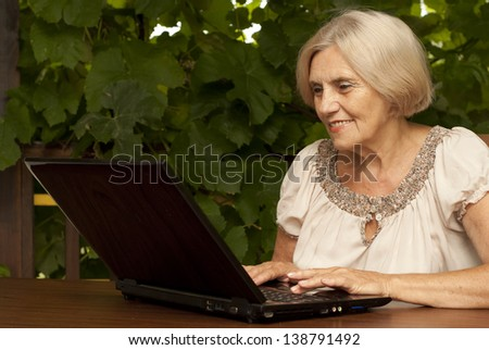 Charming older woman sitting at a table at home on the veranda - stock photo