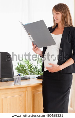 Charming pregnant female holding a file while standing in the office - stock photo