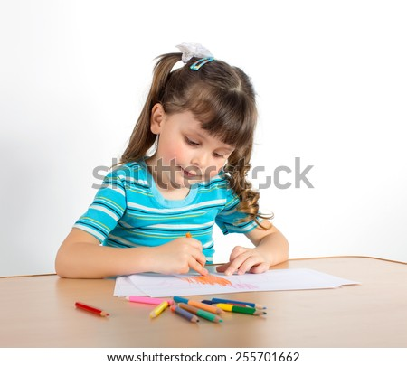Charming preschooler with pigtails draws at table. Little girl draws