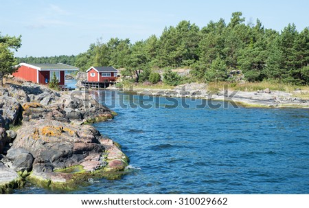Charming red cottages stand by the seaside at the east coast of Sweden - stock photo