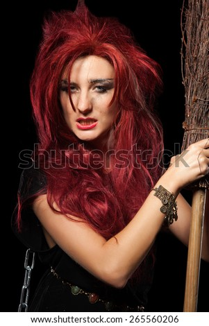 Charming red-haired witch with broom.  - stock photo