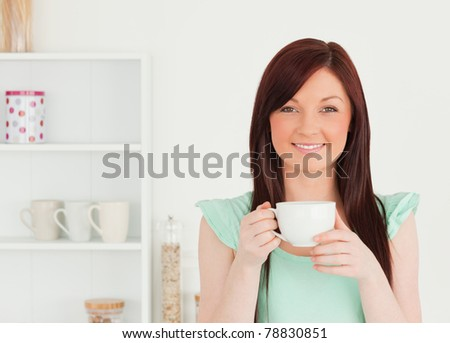 Charming red-haired woman having her breakfast in the kitchen in her apartment