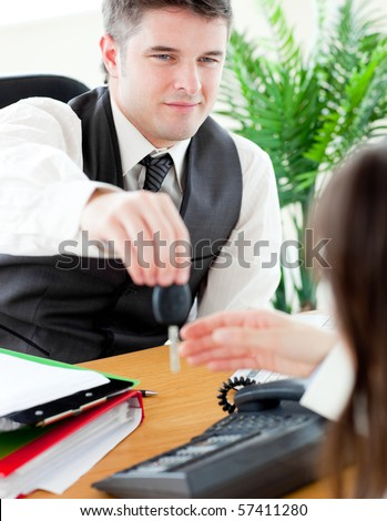 Charming salesman giving car's key to his customer  sitting in his office - stock photo