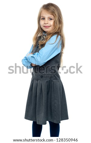 Charming schoolgirl standing sideways with her arms folded. - stock photo
