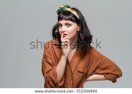 Charming sensual young woman showing silence gesture isolated over grey background - stock photo