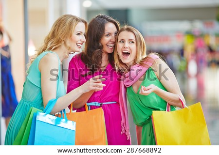 Charming shopaholics with paperbags discussing something the saw in the mall - stock photo
