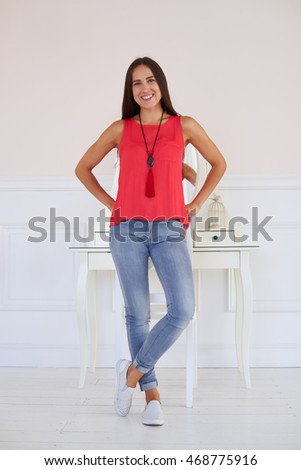 Charming slim woman in trendy light outfit posing. Wearing stylish red blouse with accessories, light-blue denim jeans and white casual shoes