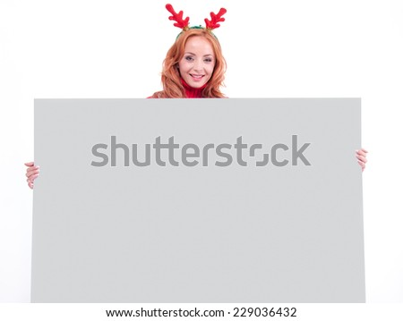 Charming smiling girl with christmas sweater holding blank paper sheet - stock photo