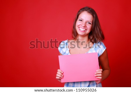 charming smiling young woman with red blank over bright red background - stock photo