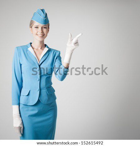 Charming Stewardess Dressed In Blue Uniform Pointing The Finger On Gray Background - stock photo
