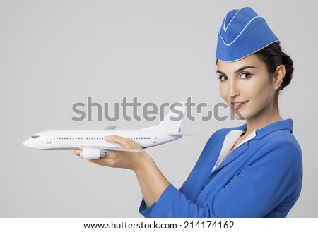 Charming Stewardess Holding Airplane In Hand. - stock photo