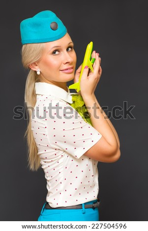 Charming Stewardess Holding Airplane In Hand - stock photo