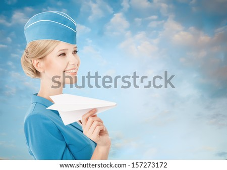 Charming Stewardess Holding Paper Plane In Hand. Blue Sky Background.  - stock photo