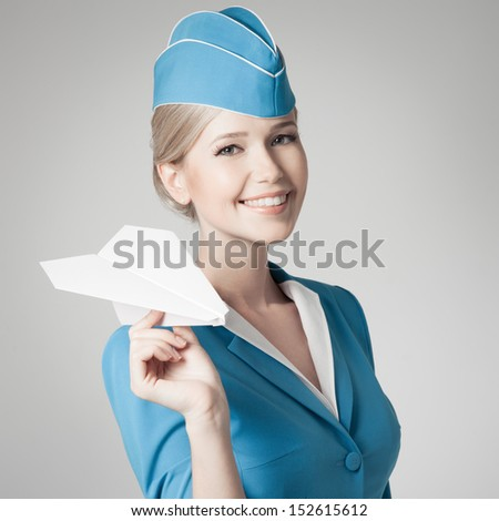 Charming Stewardess Holding Paper Plane In Hand. Gray Background. - stock photo