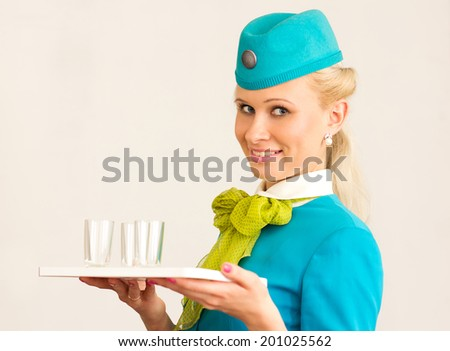 Charming Stewardess Holding tray with glasses In Hand. - stock photo