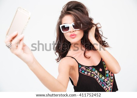 Charming stylish woman making selfie photo on smartphone isolated on a white background - stock photo