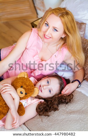 Charming, sweet, beautiful little girl in a nightgown, hugging a teddy bear lying on the bed with irresistible mother. Happy childhood. background, closeup, macro
