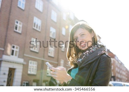 charming sweet caucasian girl with her phone in the urban life - stock photo