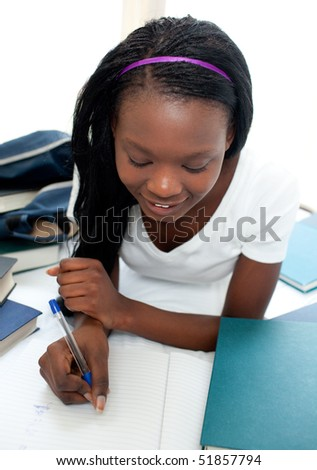 Charming teen girl studying lying on her bed at home - stock photo