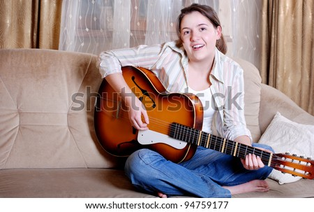 Charming teenage girl play and singing by guitar sitting on the sofa at home