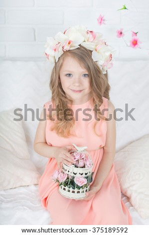 Charming tender pretty blonde caucasian girl in orchid floral hairband wreath holds cell with flowers - stock photo