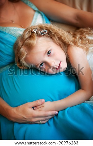 Charming toddler girl holds her head on the belly of her pregnant mother and smiling - stock photo