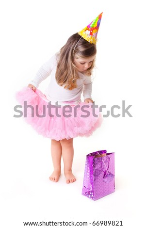 Charming two years old girl in birthday hat looking a gift - stock photo