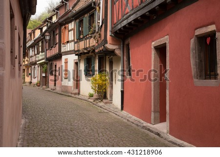 Charming village in Alsace France with colorful old buildings and cobblestone street - stock photo