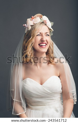 Charming vivacious young bride in a strapless white wedding dress and veil with flowers in her hair standing laughing, upper body over grey - stock photo