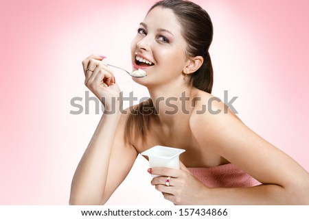 Charming woman eating yogurt / studio photography of brown-eyed brunette girl holding spoon and a container of yogurt - isolated on background  - stock photo