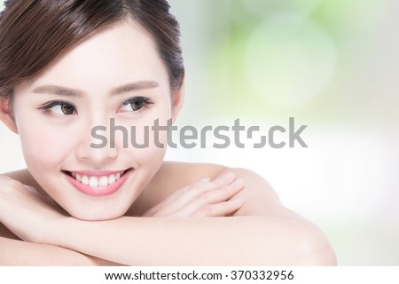 Charming woman face Smile to you close up while lying with nature green background, asian girl