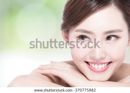 Charming woman face Smile to you close up while lying with nature green background, asian girl - stock photo