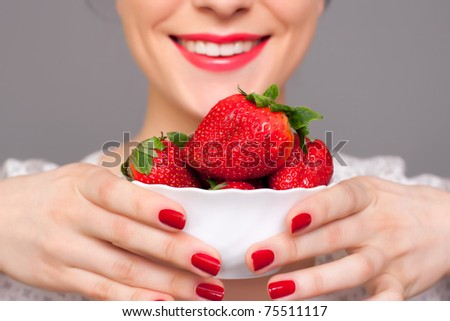 Charming woman holding a plate with a lot of strawberries - stock photo