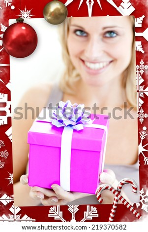 Charming woman holding a present in front of her with christmas themed page - stock photo
