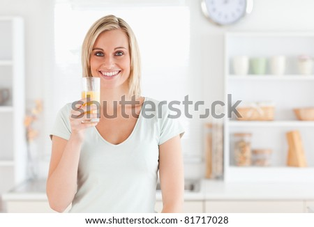 Charming woman holding glass filled with orange juice while standing looking into the camera in the kitchen - stock photo