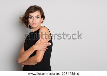 Charming woman in black on a gray wall. Woman 36 years old. - stock photo