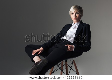 Charming woman in fashion cloth sitting on the chair over gray background and looking at camera - stock photo