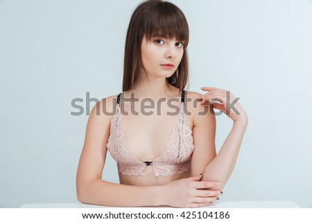 Charming woman in lingerie sitting at the table isolated on a white background and looking at camera - stock photo