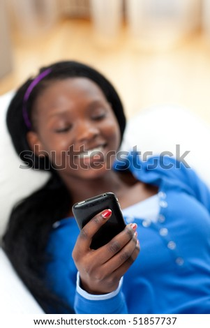 Charming woman sending a text lying on a sofa in the living-room - stock photo