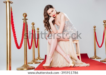 Charming woman sitting on the chair and looking at camera on red carpet - stock photo