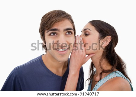 Charming woman whispering something to her fiance against a white background