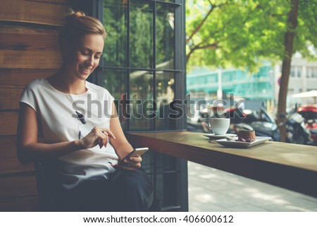 Charming woman with beautiful smile reading good news on mobile phone during rest in coffee shop, happy Caucasian female watching her photo on cell telephone while relaxing in cafe during free time  - stock photo