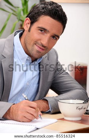 charming 30 years old man dressed in a grey suit and writing in a cosy place - stock photo