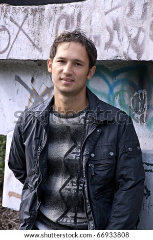 charming young adult in a jacket has leaned the elbows on a wall from graffiti, outside - stock photo