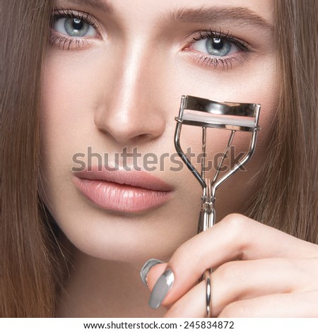 Charming young babe with curler and light makeup. Picture taken in the studio - stock photo
