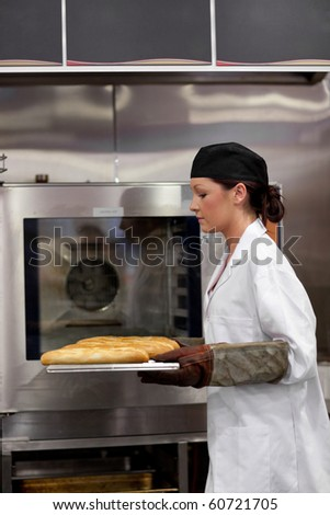Charming young baker with baguettes in the kitchen