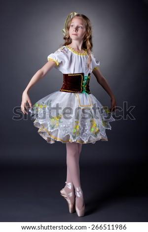Charming young ballerina dancing in folk costume - stock photo