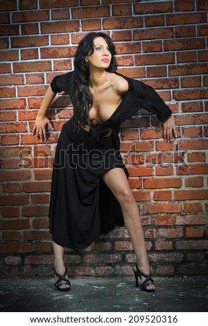 Charming young brunette woman in black and high heels staying near a red brick wall. Sexy gorgeous young woman near old wall. Full length portrait of a provocative woman with long hair and high heels - stock photo